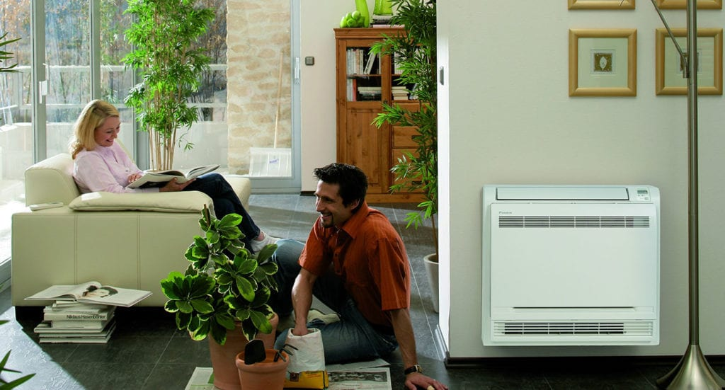 Woman and man sitting in living room next to ductless mini split system.