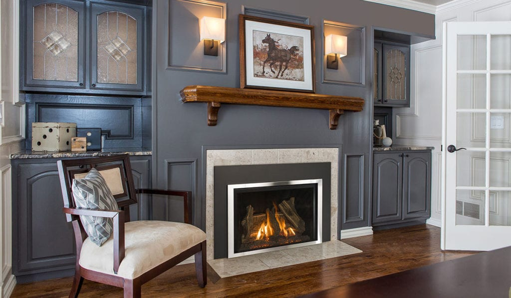 A lit gas fireplace in a traditional living room with gray walls and gray cabinets on each side.