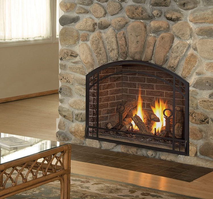 A fireplace roars inside a mantel with large stones. The living room is traditional with tan, beige and brown tones.