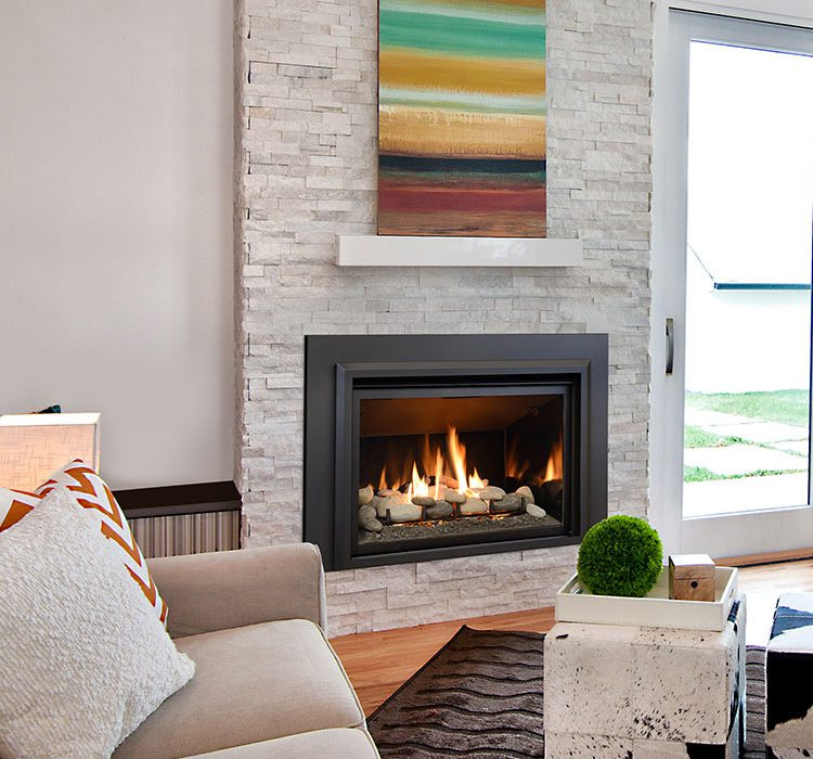 A gas fireplace roars in the center of a living room with light walls and furniture.