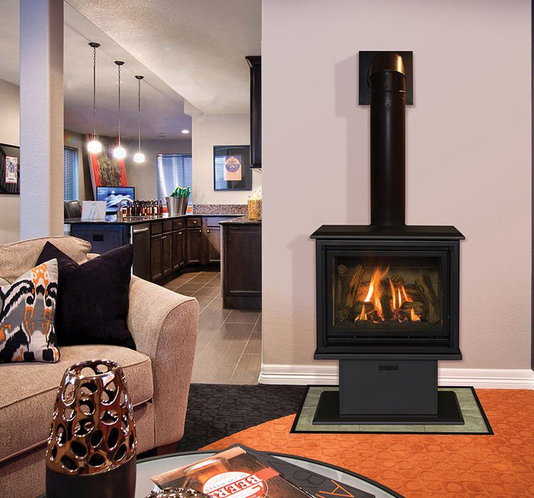 A small, rectangular gas stove is lit up on a side wall of a small living room.