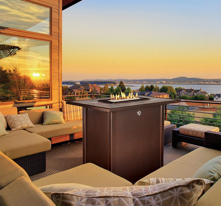 A tall, rectangular outdoor gas fireplace sits ablaze in the middle of a large deck with light brown patio furniture.