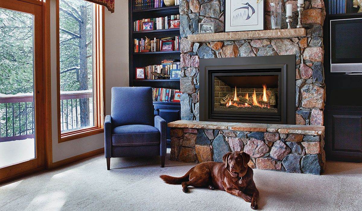 A gas fireplace insert is lit inside a mantel made of large, multi-colored stones. A brown dog relaxes in front of the fire.