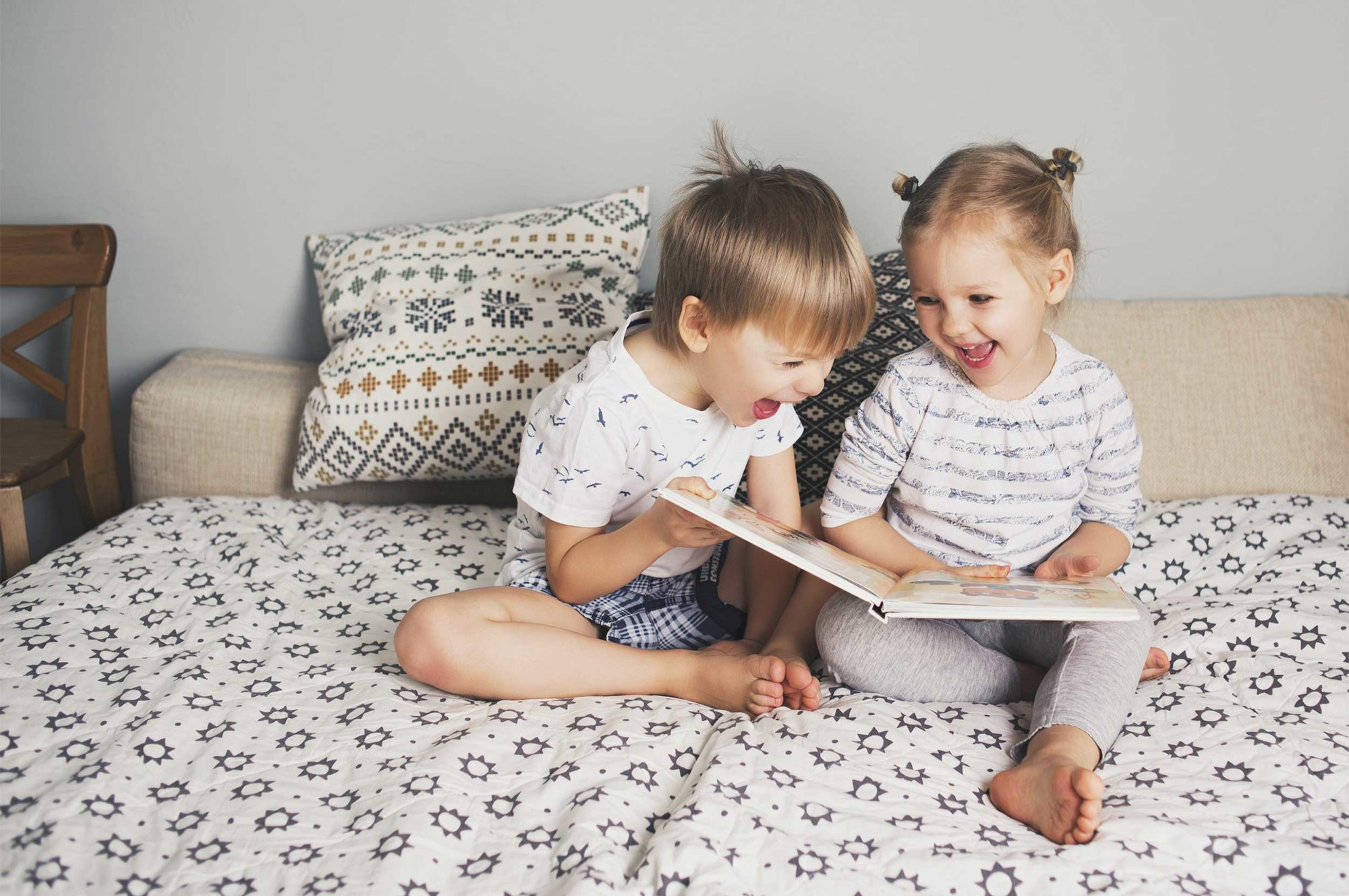 A young boy and girl sit on bed laughing and reading a book