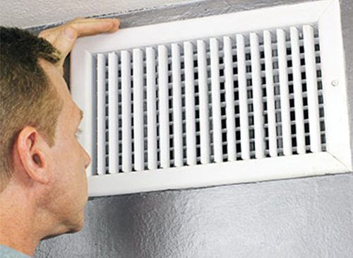 Man inspecting vent of home heating and cooling ductwork.