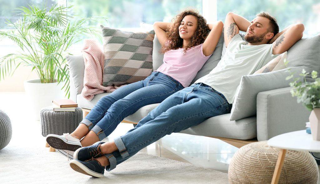 A young man and woman relaxing on a couch in a living room