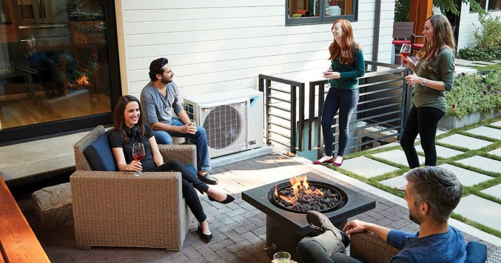 A group of friends socializing on a modern outdoor patio with a Daikin FIT unit in the background