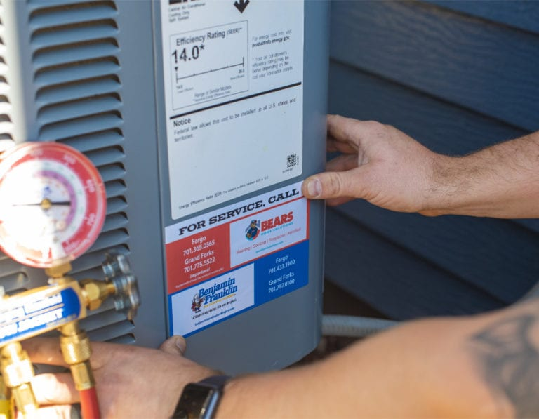 A closeup of a technician's hands placing a service sticker on an outdoor air conditioner