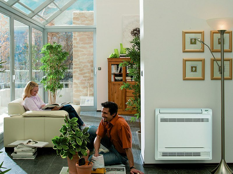 A man and a woman relaxing near a mini split air conditioner in their living room