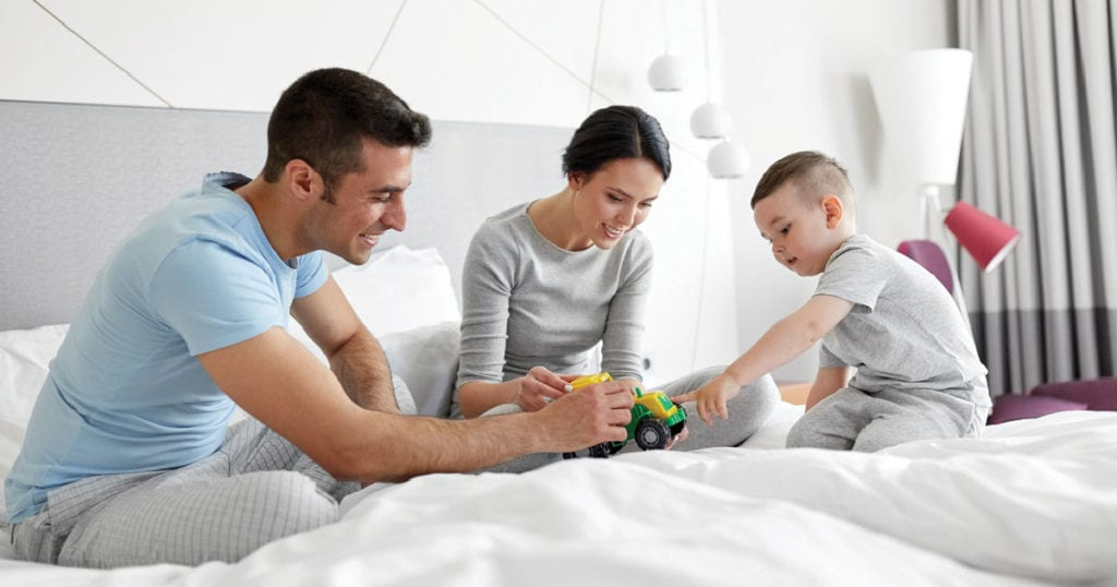 A father, mother, and son sit on a large bed and look at a toy truck together