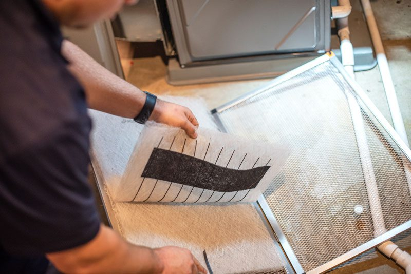 A closeup of a male Bears Home Solutions HVAC technician changing the air filters in a home furnace
