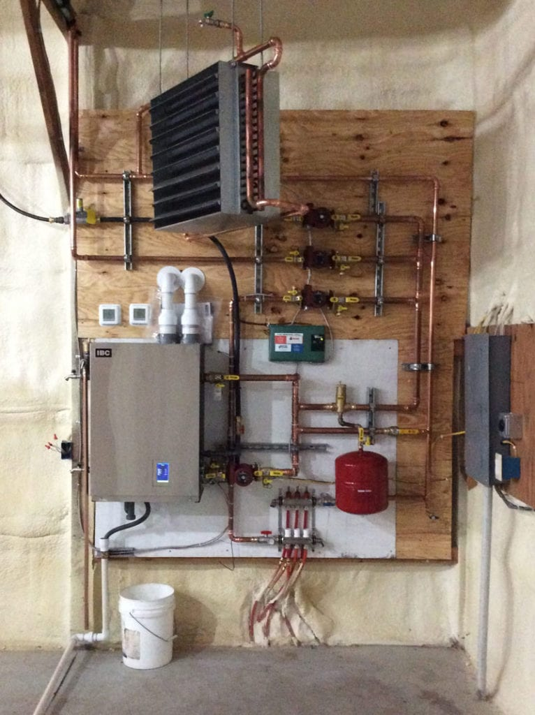 A modern home boiler hanging on a wooden wall surrounded by pipes