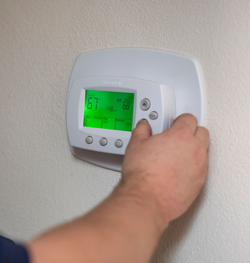 A closeup of a man's hand adjusting a thermostat on a white wall in a home
