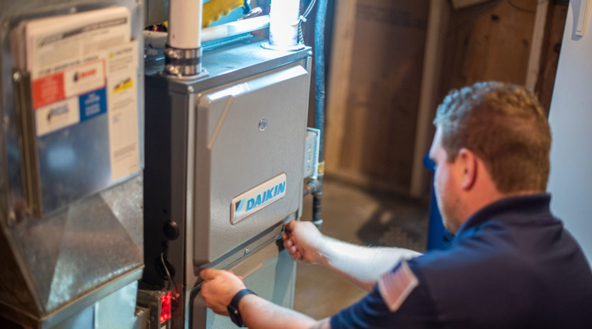 A male Bears Home Solutions heating and cooling technician removes the front panel of a Daikin furnace during an inspection