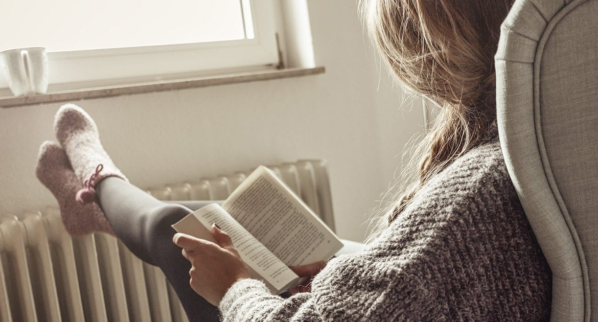 Woman facing the window reads book in chair with feet resting on heat radiator.
