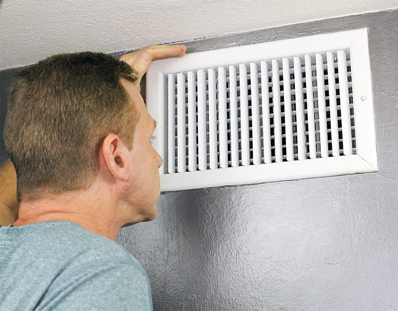 Man looks into open house vent.