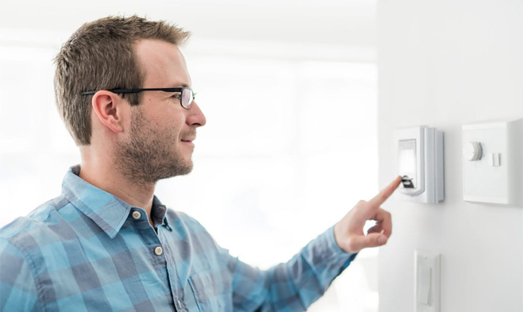Man presses button on in-home thermostat.