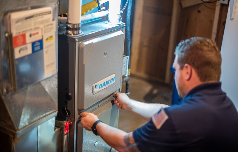 A heating and cooling specialist checks efficiency of air conditioning unit.