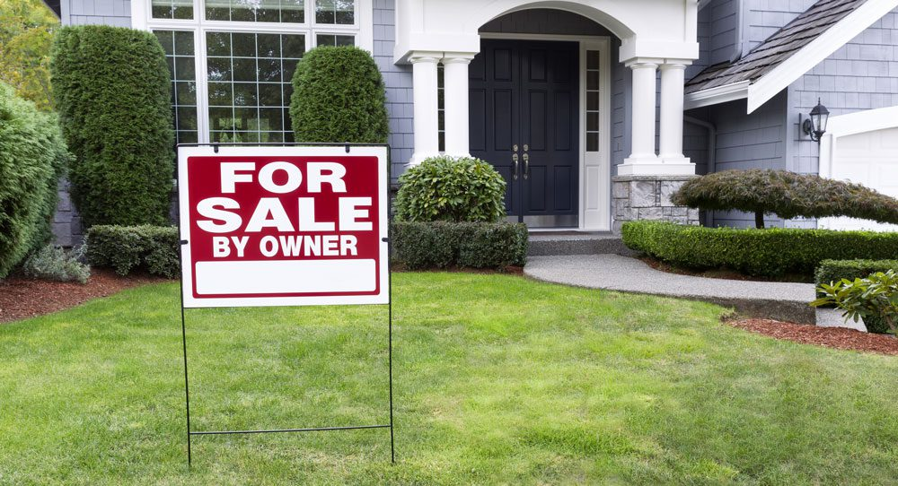 """""""For Sale By Owner"""" sign outside of house."""