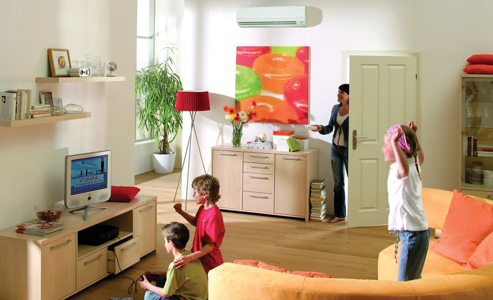 Three children playing in a modern living room while a mom adjusts the temperature on a ductless mini split air handler in the background