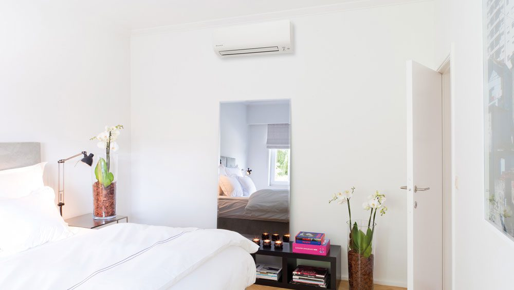 A brightly lit bedroom with a mini split air handling unit on the wall