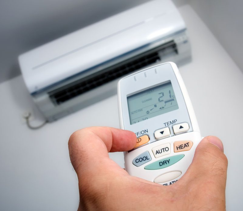 A hand holding a remote control turns on an air conditioning unit on a white wall.