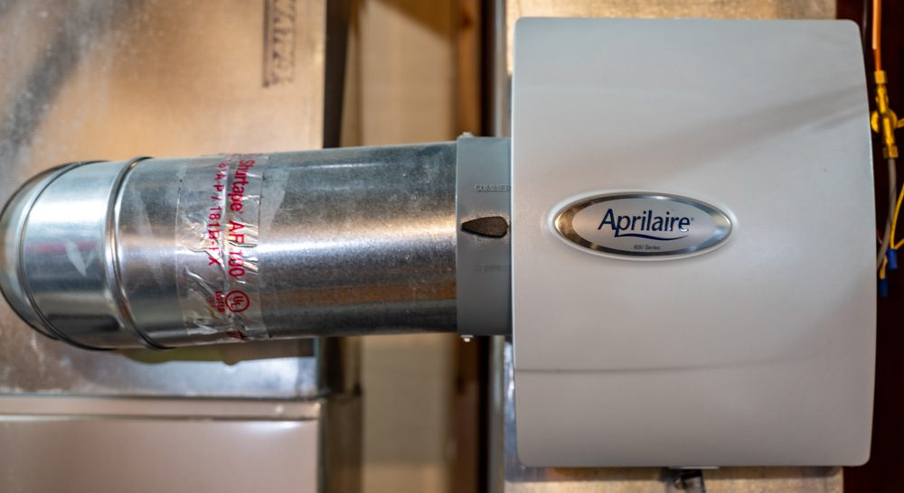 A whole-home Aprilaire humidifier in the mechanical room of a house.