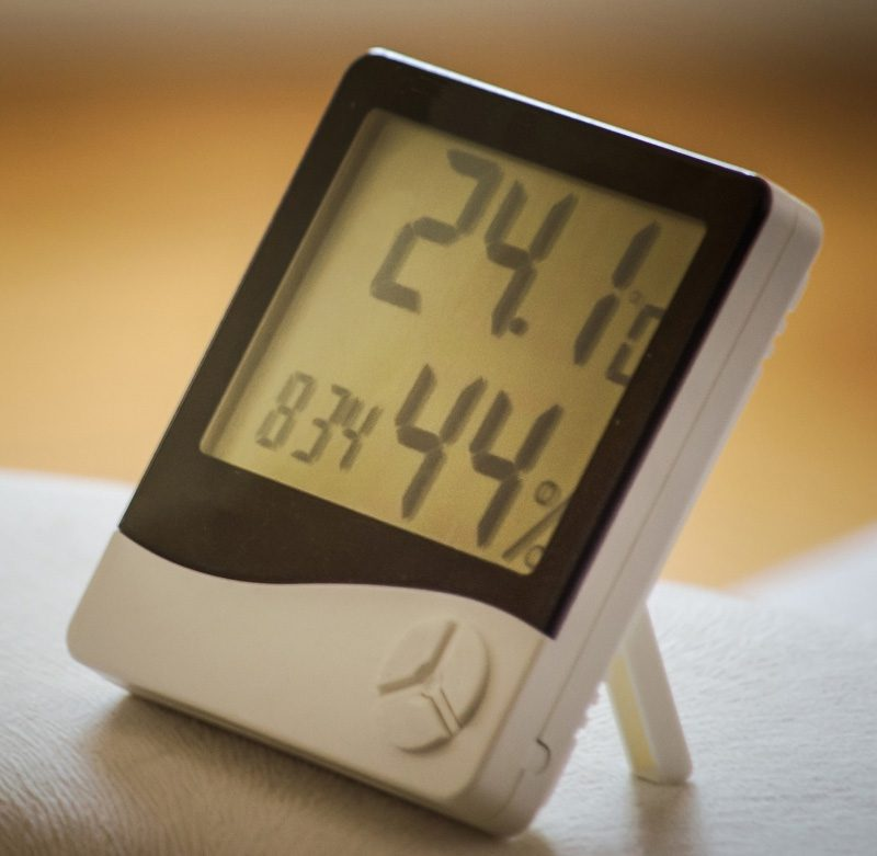 A white hygrometer showing measurements of humidity in a home